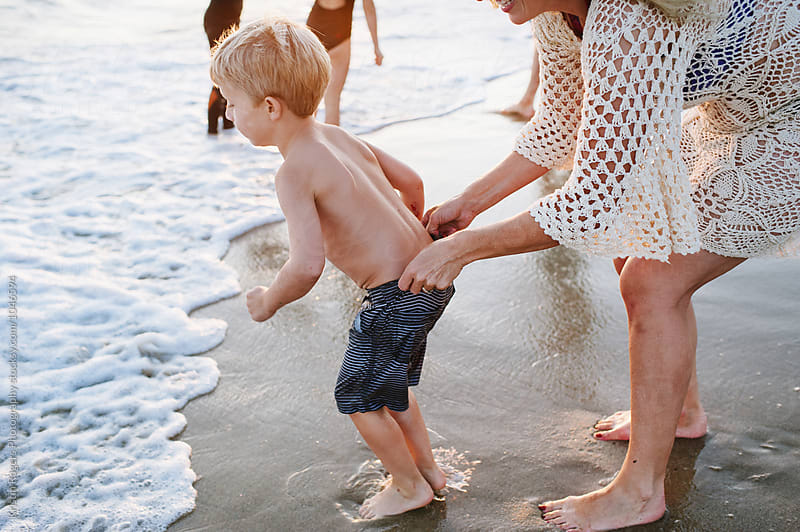 Mother on beach with family pulling up sons shorts by Kristin Rogers Photography for Stocksy United