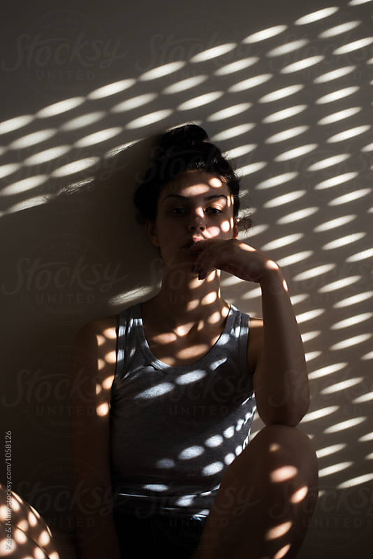 Portrait of beautiful woman with light on her skin by Katarina Simovic for Stocksy United