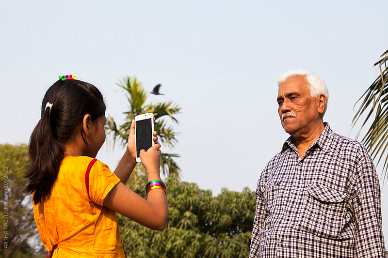Grandchildren taking photo of Grandfather with smartphone by PARTHA PAL for Stocksy United