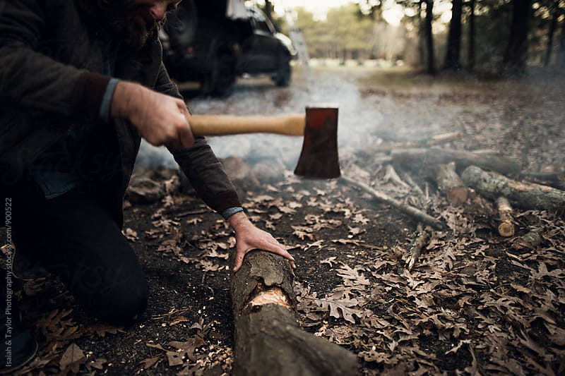 Man using an axe to cut wood by Isaiah & Taylor Photography for Stocksy United