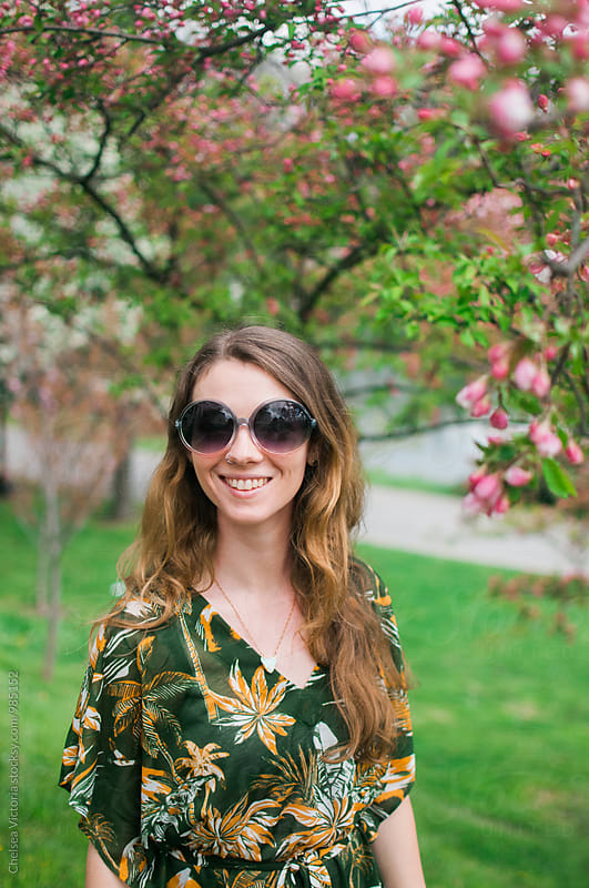 A young woman standing under a blooming tree by Chelsea Victoria for Stocksy United