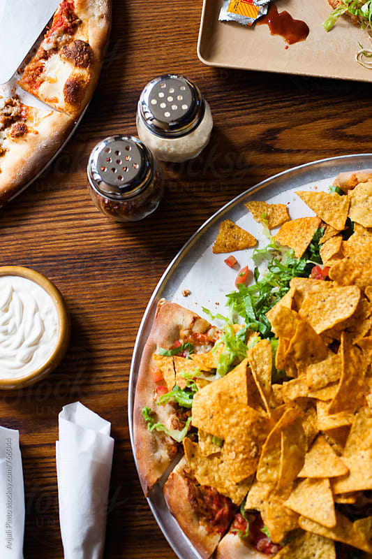 Taco Pizza with Red Pepper and Cheese Shakers by Anjali Pinto for Stocksy United
