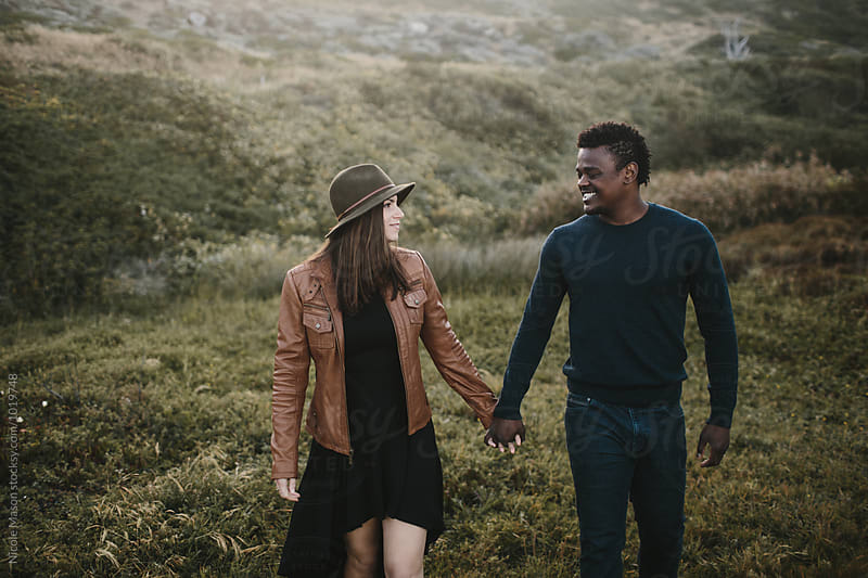 beautiful fashionable couple walking through field holding hands by Nicole Mason for Stocksy United