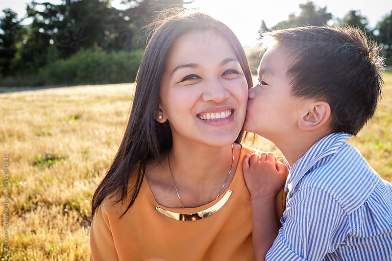 Asian kid kissing his mom on the cheek outdoor in a park by Suprijono Suharjoto for Stocksy United