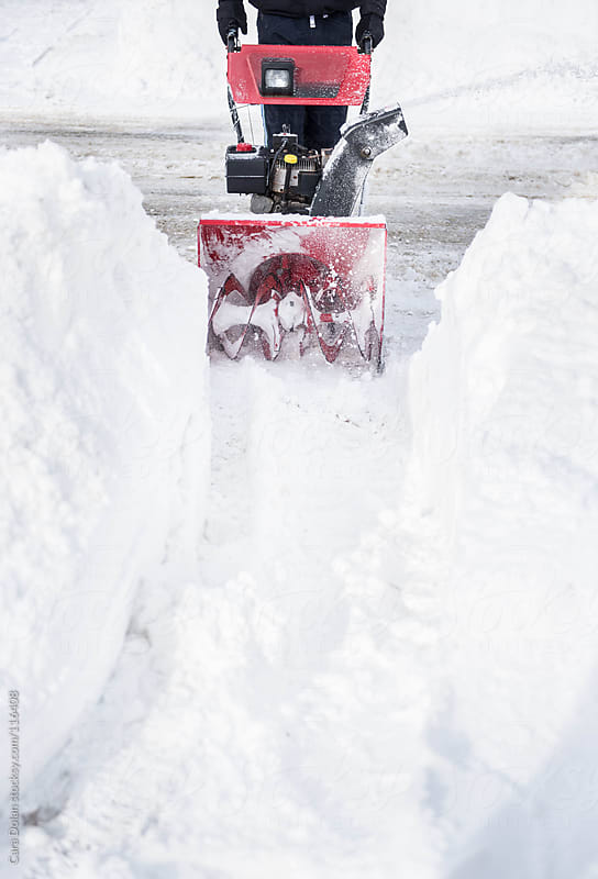 Man forges a path through deep snow with a snow blower by Cara Dolan for Stocksy United