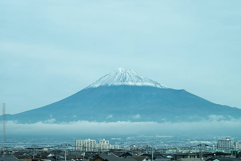Mount Fuji overshadowing city below it by Rowena Naylor for Stocksy United