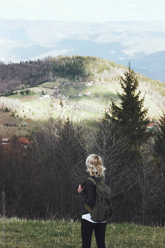 Young woman hiking and standing on top of the hill by Jovana Rikalo for Stocksy United