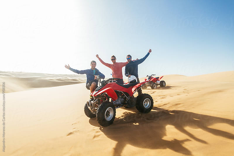 Three men smiling at camera near quad bike in desert by Alejandro Moreno de Carlos for Stocksy United