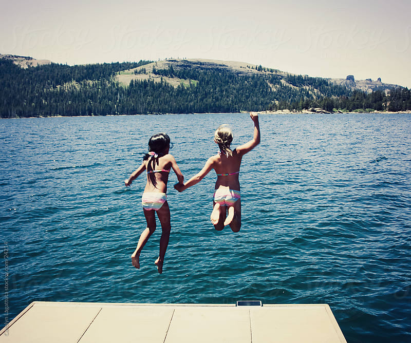 Girls jumping off the dock and holding hands during summertime by Carolyn Lagattuta for Stocksy United