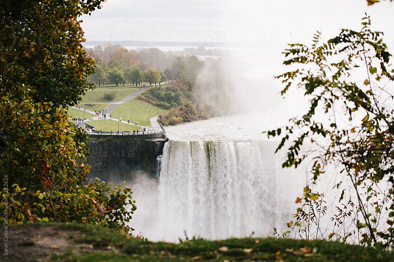 Niagara Falls through autumn trees  by Sarah Lalone for Stocksy United