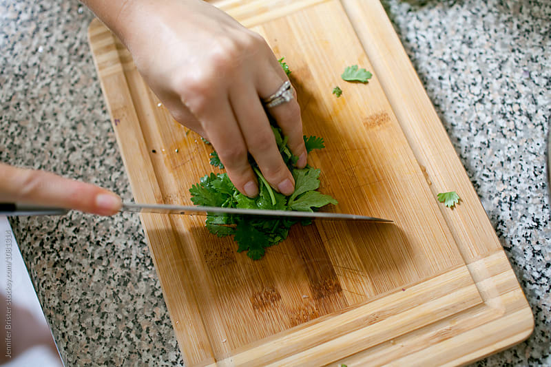 Woman chopping cilantro by Jennifer Brister for Stocksy United