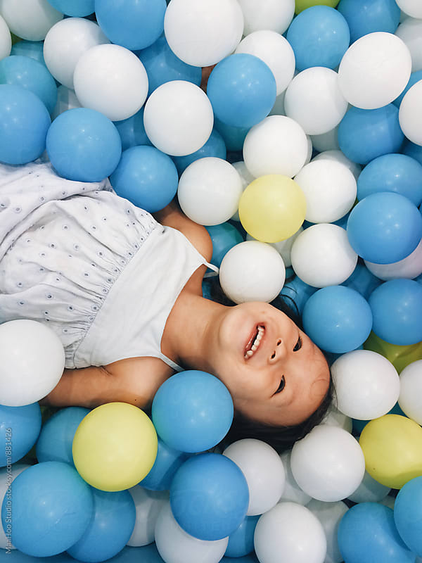 Toddler girl playing in ocean balls by Maa Hoo for Stocksy United