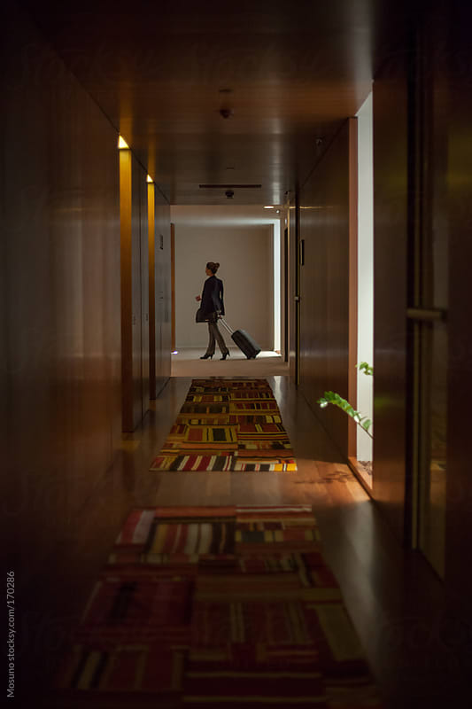 Anonymous Woman Walking Down the Hotel Hallway by Mosuno for Stocksy United
