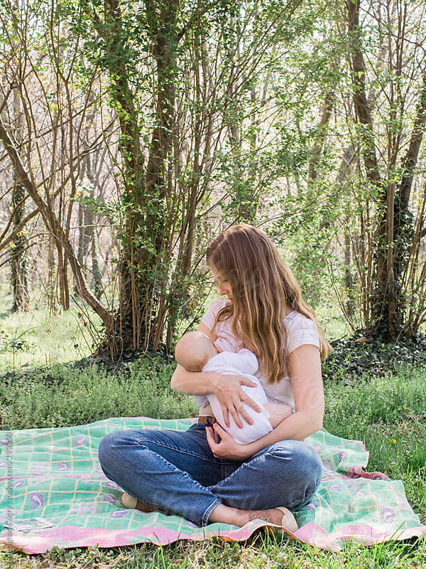 mom breastfeeding baby under spring blooms by Meaghan Curry for Stocksy United