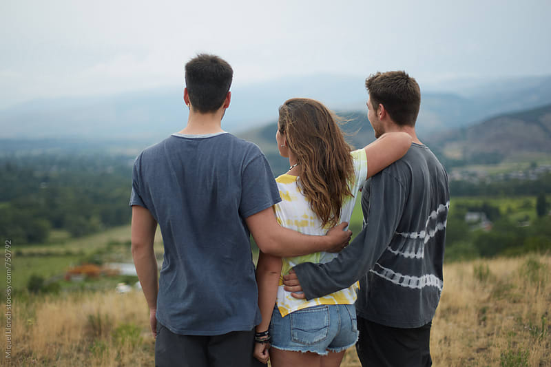 Back view of three teenagers watching the landscape by Miquel Llonch for Stocksy United