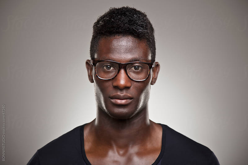 African young real man with glasses over grey background by BONNINSTUDIO for Stocksy United