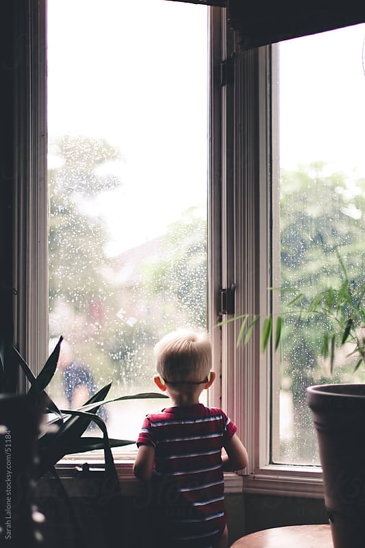 Little boy looking out the window on a rainy day. by Sarah Lalone for Stocksy United