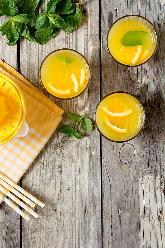 Drinks: orange juices, mint leaves, straws and citrus juicer from above by Pixel Stories for Stocksy United