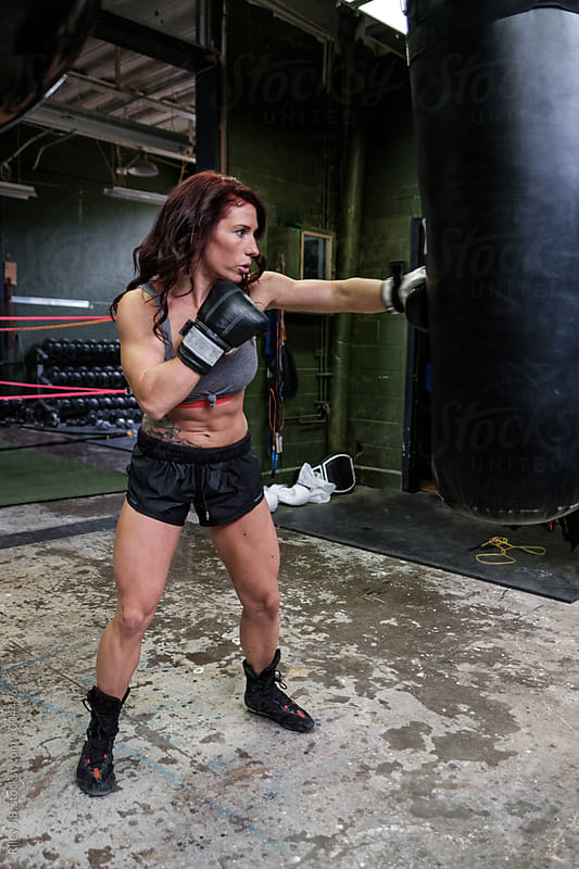 A muscular woman strikes a punching bag in a gritty gym by Riley J.B. for Stocksy United
