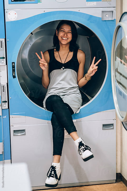 Young Asian Woman having fun inside a huge washing machine by Juri Pozzi for Stocksy United