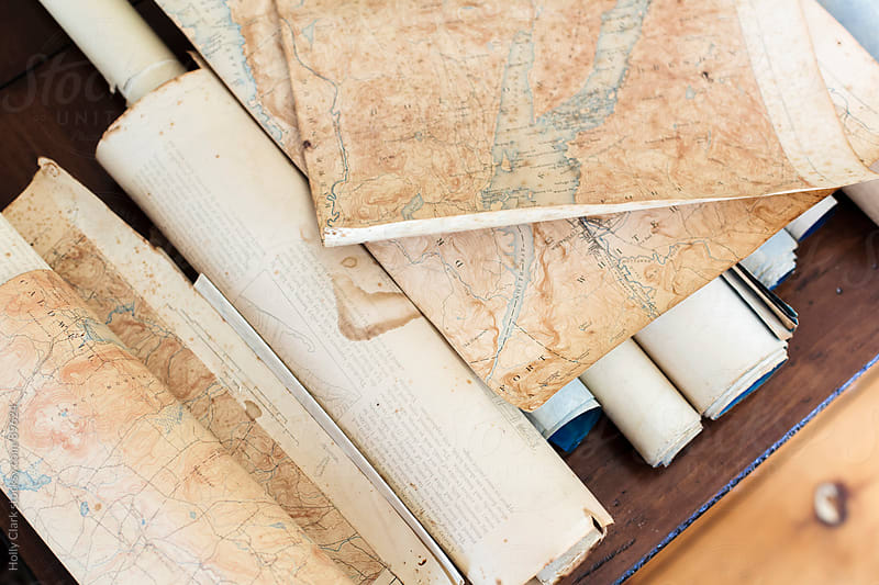 Looking down on pieces of antique maps and scrolls. by Holly Clark for Stocksy United