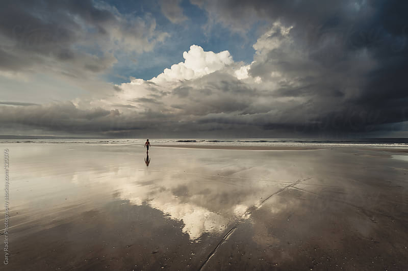 Solitary Man walking towards Water at Low Tide by Gary Radler Photography for Stocksy United