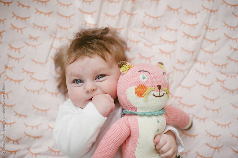 Cute baby girl with finger in mouth hugging cat doll by Kristin Rogers Photography for Stocksy United