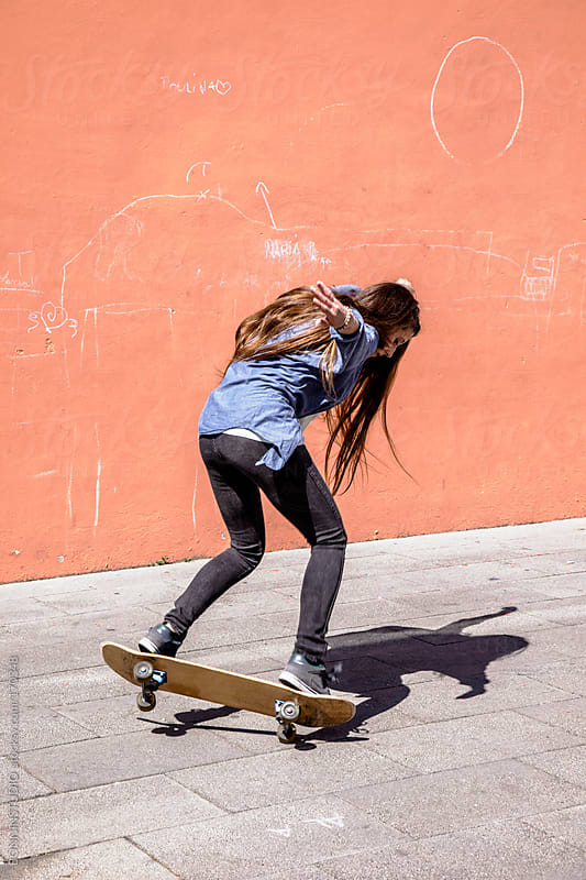 Young skater girl skating in front a colorful wall. by BONNINSTUDIO for Stocksy United