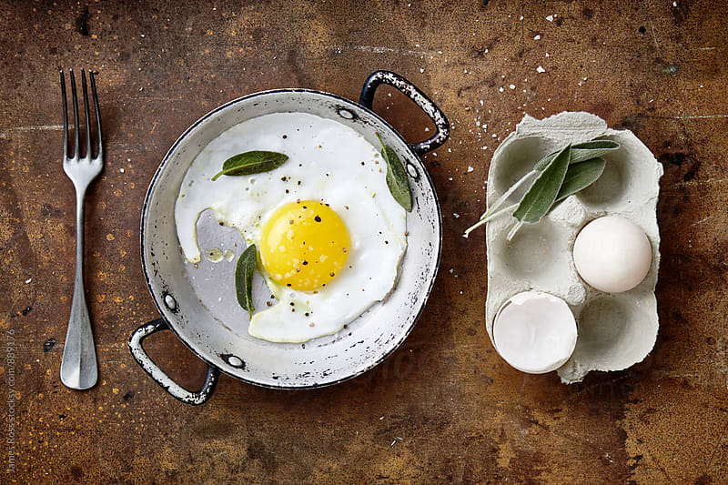 A single cooked duck egg in a pan by James Ross for Stocksy United