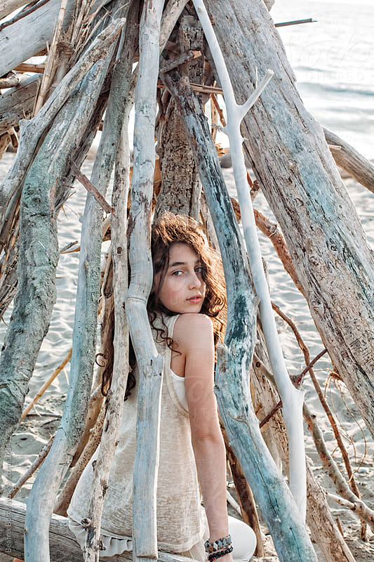 Girl on the beach under a tent made of tree trunks and branches by Beatrix Boros for Stocksy United