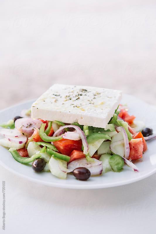 Fresh greek salad on white plate by Alberto Bogo for Stocksy United