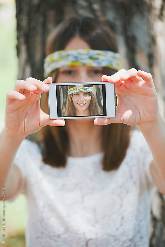 Woman taking a self-portrait with the camera on her cell phone by BONNINSTUDIO for Stocksy United