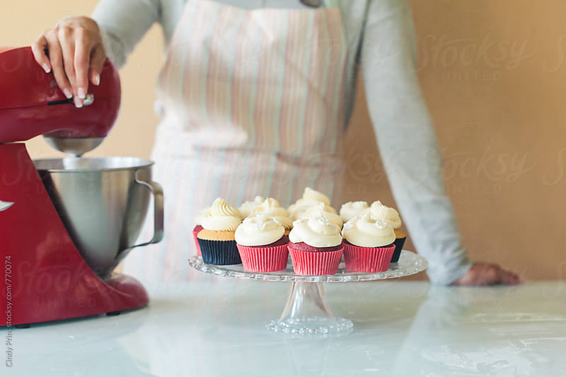 Body of woman in apron behind a tray of cupcakes and a mixer by Cindy Prins for Stocksy United