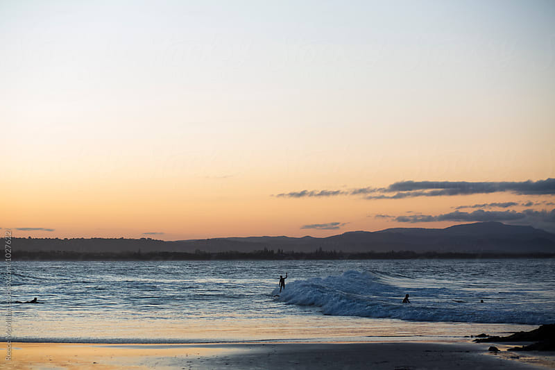 A surfer at Byron Bay celebrates on a wave by Reece McMillan for Stocksy United