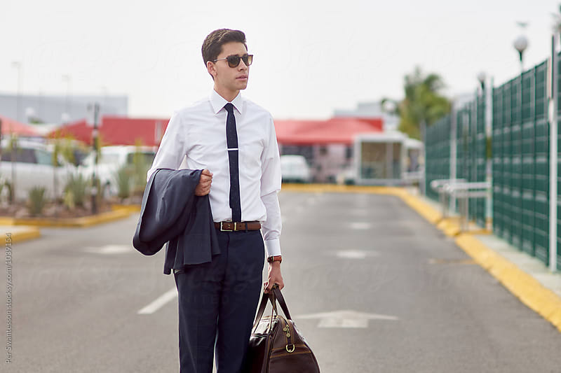 Young man standing at airport parking lot by Per Swantesson for Stocksy United