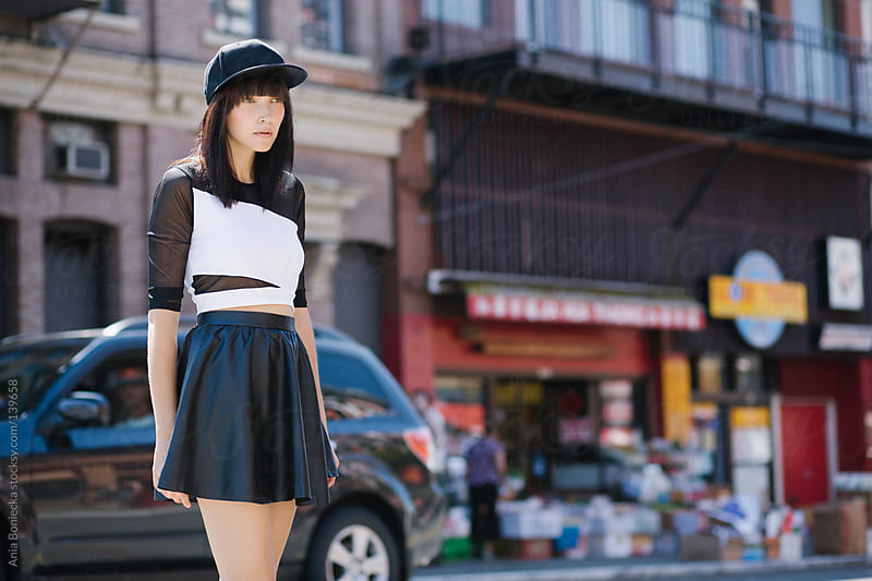 A woman in a leather skirt on a city street by Ania Boniecka for Stocksy United