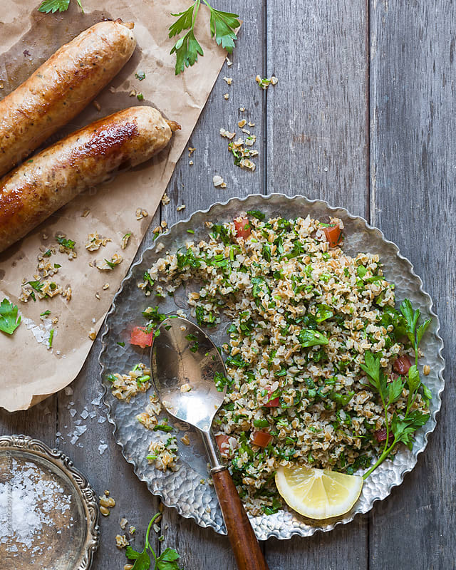 Healthy homemade tabbouleh salad with grilled sausages by Trent Lanz for Stocksy United