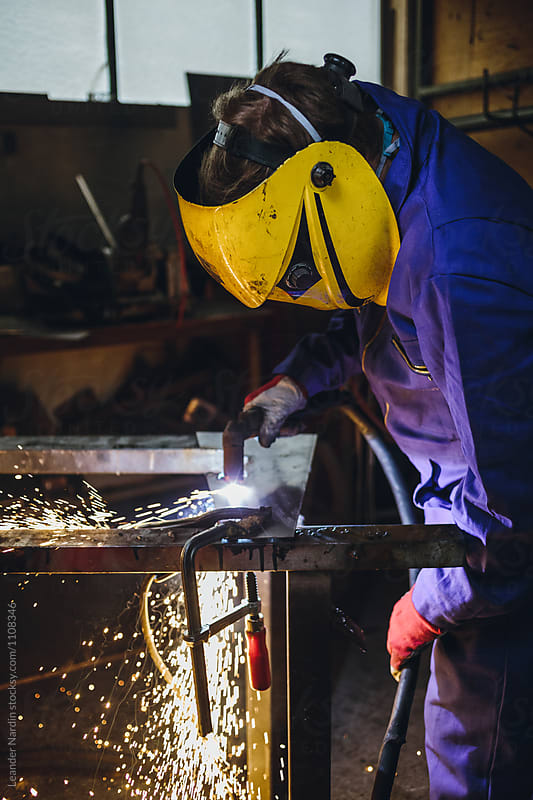 metal worker with plasma cutter and yellow protection mask