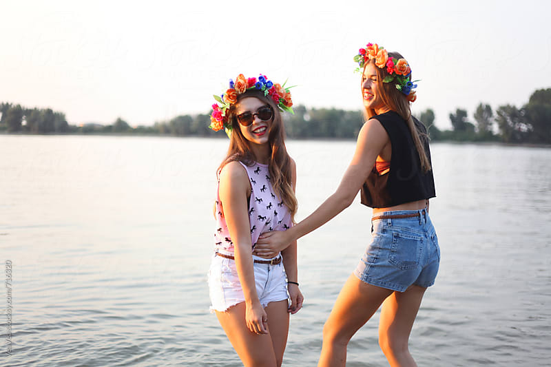 Two beautiful female friends having a good time by the river  by Marija Mandic for Stocksy United