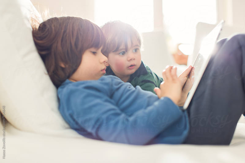 1 year old boy and his 5 year old brother looking a digital tablet by Nasos Zovoilis for Stocksy United