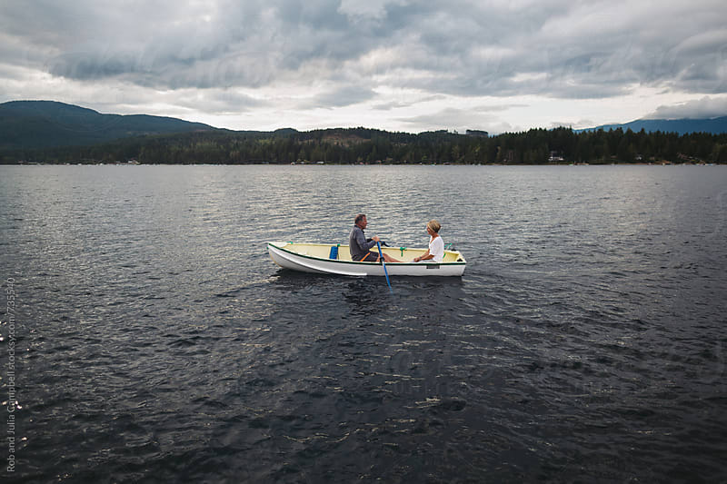 Mature couple rowing together on lake by Rob and Julia Campbell for Stocksy United