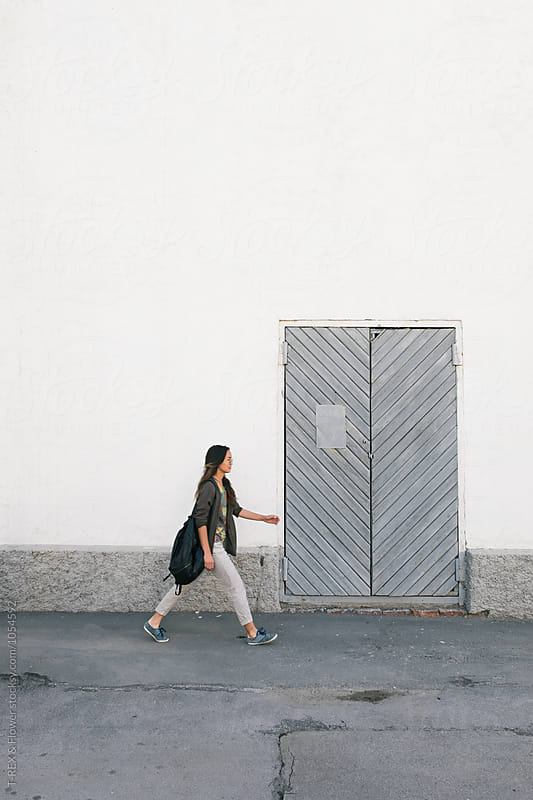 Stylish girl with rucksack walking along the street by Danil Nevsky for Stocksy United