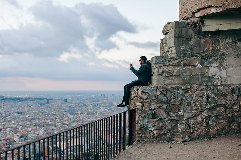 Man sitting above city taking a photo with his phone. by BONNINSTUDIO for Stocksy United