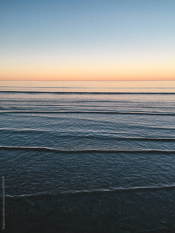 Low waves in calm water at sunset by Angela Lumsden for Stocksy United