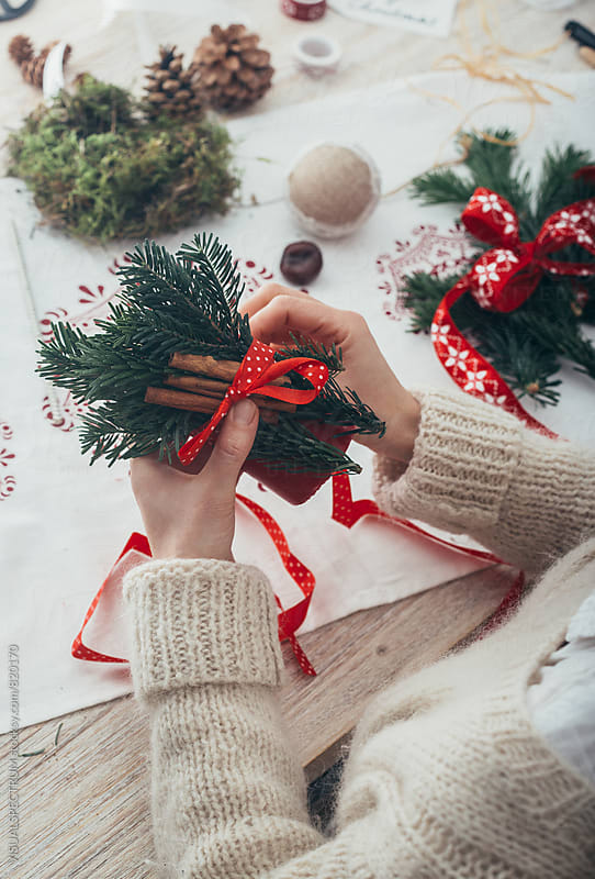 DIY Christmas - Woman Tying Cinnamon Sticks and Fir Twigs to Big Red Candle by VISUALSPECTRUM for Stocksy United