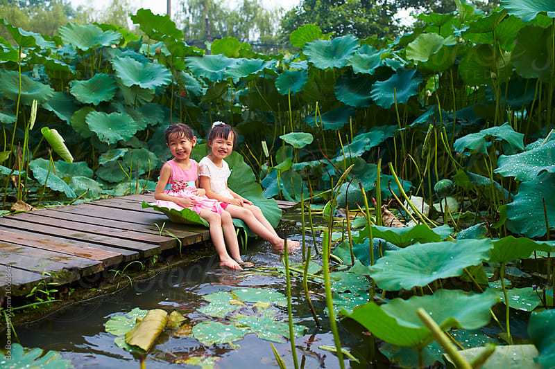 three lovely little girls sitting by the  lotus pond by cuiyan Liu for Stocksy United