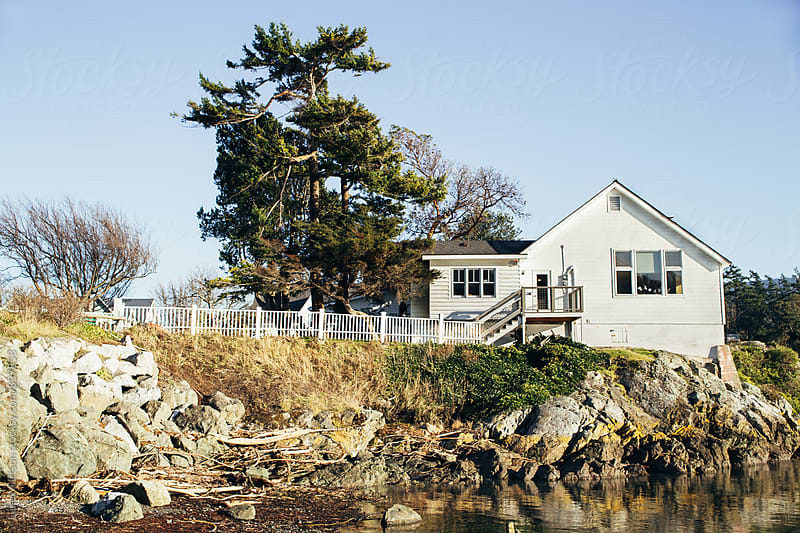 White Beach Cabin On Edge Of Rocky Ocean Shore by Luke Mattson for Stocksy United