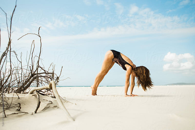 Women doing yoga on empty sandy beach  by Tahl Rinsky for Stocksy United