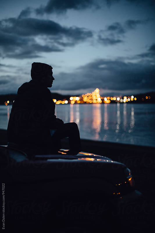 Man Sitting On Car by River at Dusk by Evan Dalen for Stocksy United