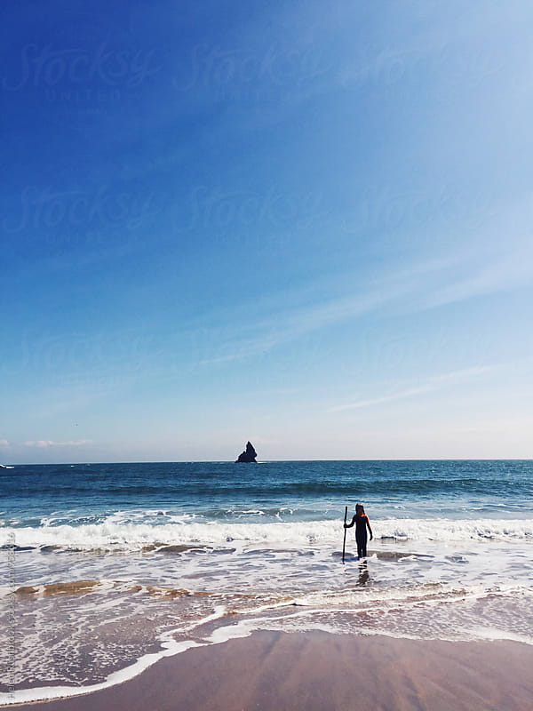 Small child standing in the sea with Church Rock in the background. by Helen Rushbrook for Stocksy United
